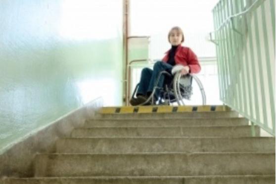 Persona en silla de ruedas en lo alto de una escalera