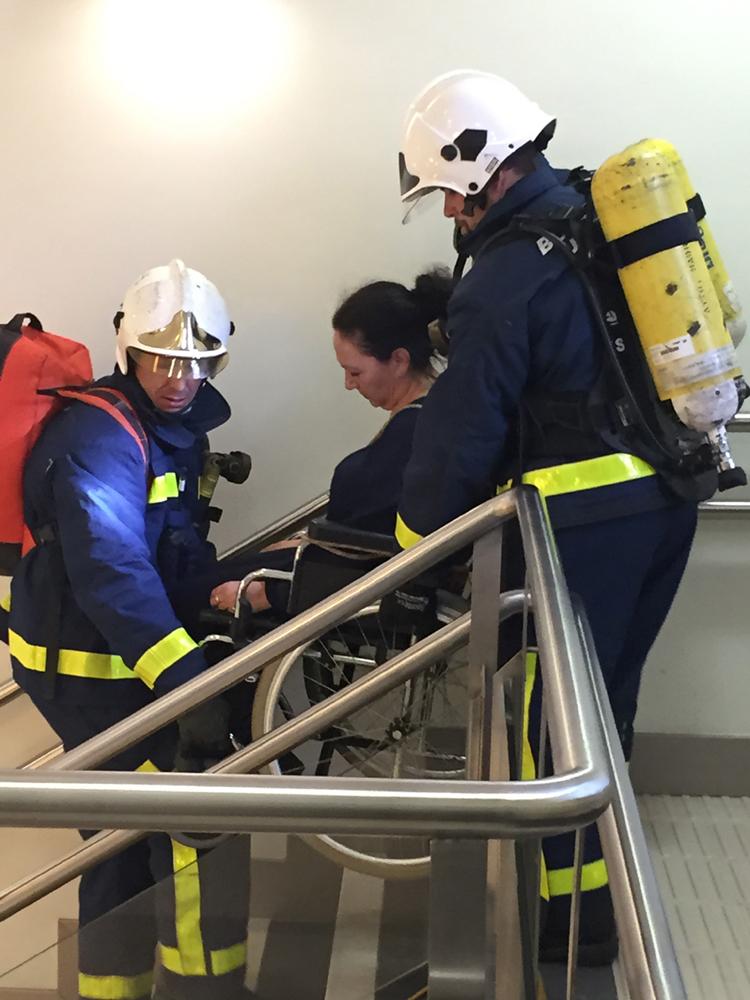 bomberos evacuando a una persona con discapacidad motora.