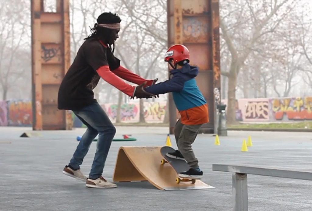 Hombre ayudando a un niño a subir una difícil rampa.