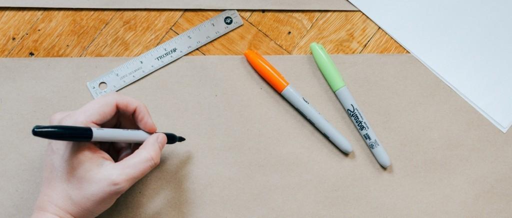 Una mano sostiene un lapiz en actitud de dibijar sobre un gran papel en blanco y sobre la mesa hay otras herramientas como lápices de colores, regla de dibujo, etc