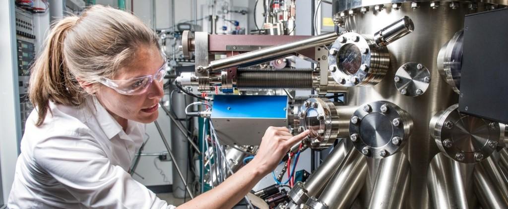 Una mujer con gafas de protección realiza tareas de mantenimiento en una compleja maquinaria de un edificio.