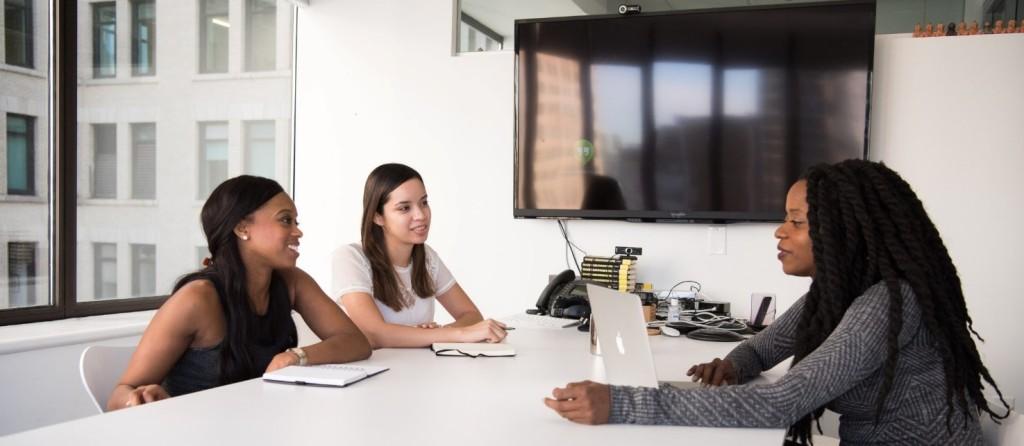 Dos mujeres reunidas en torno a una mesa de trabajo en un ambiente de oficina, escuchan las recomendaciones de una tercera.